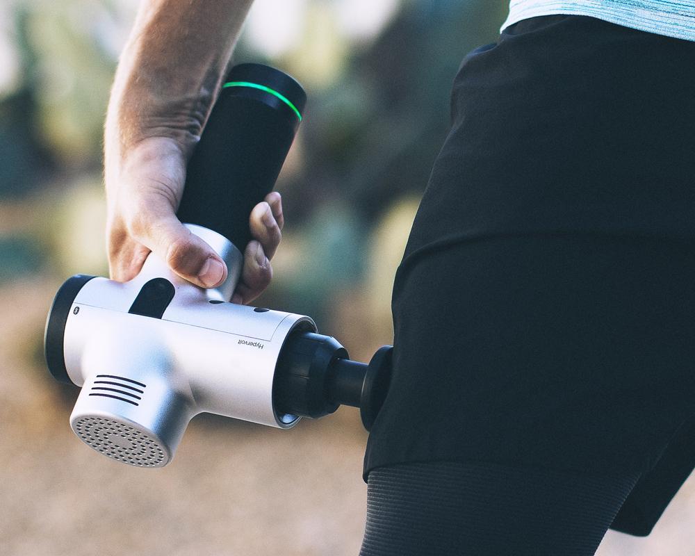 Massage gun on thigh muscle
